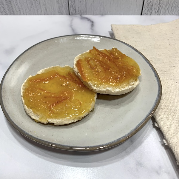 gluten free vegan English muffin split open on a grey plate and covered with homemade marmalade