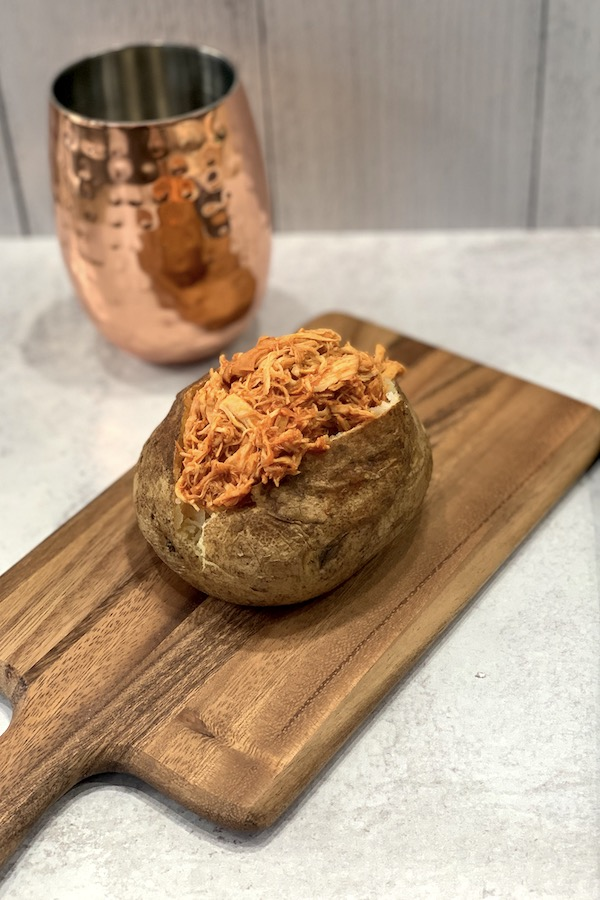 instant pot shredded bbq chicken in a baked potato on a wooden serving board with a copper glass