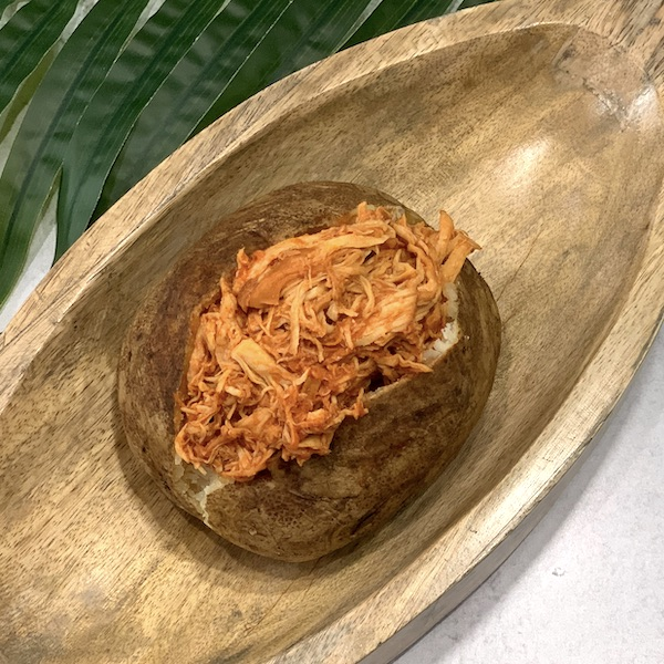 one pot shredded bbq chicken in a baked potato on a wooden platter with a palm leaf