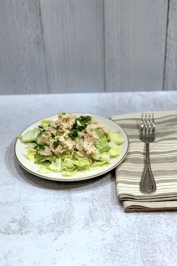 shredded italian chicken on a salad on a white plate with a striped taupe napkin