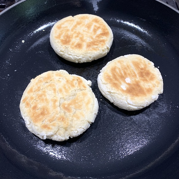 3 gluten free vegan english muffins cooking in a cast iron skillet on the stove