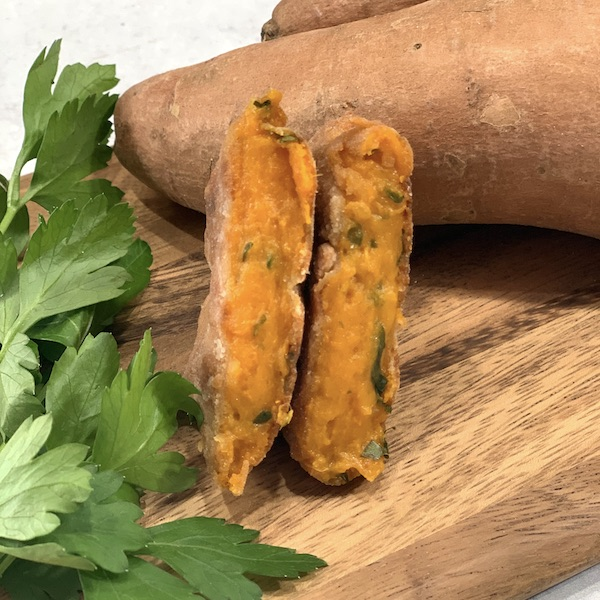 a vegan sweet potato cake that was made in the air fryer cut in half to show the inside on a wooden cutting board with a whole sweet potato and bunch of parsley