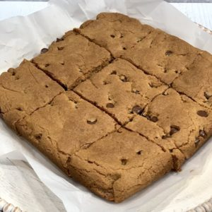 finished gluten free blondie recipe cut into 9 squares on white parchment paper