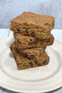 stack of gluten free blondies with chocolate chips on a white plate