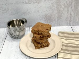 stack of gluten free dairy free blondies on a white plate with a mixing bowl in the background